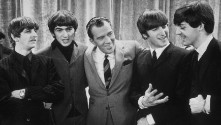 Ed Sullivan (center) smiles while standing with The Beatles on the set of his variety show on February 9, 1964.