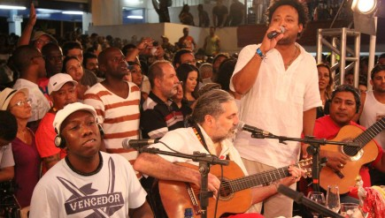 Sitting around what looks like a conference table with a small group of musicians, guitarist Moacyr Luz (center) leads his samba group.